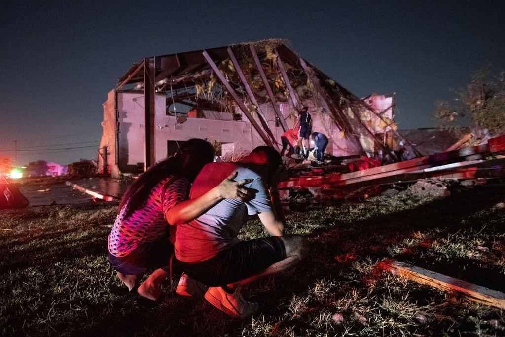Henry Ramirez, miembro de la Primera Iglesia Dallas, es consolado por su madre luego del daño que un tornado dejó a la iglesia, el domingo.