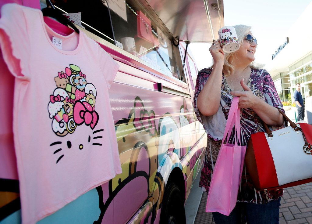Lisa Russell holds up a mug in front of the Hello Kitty food truck at The Shops at Willow Bend in Plano, Texas, Saturday, Nov. 12, 2016.
