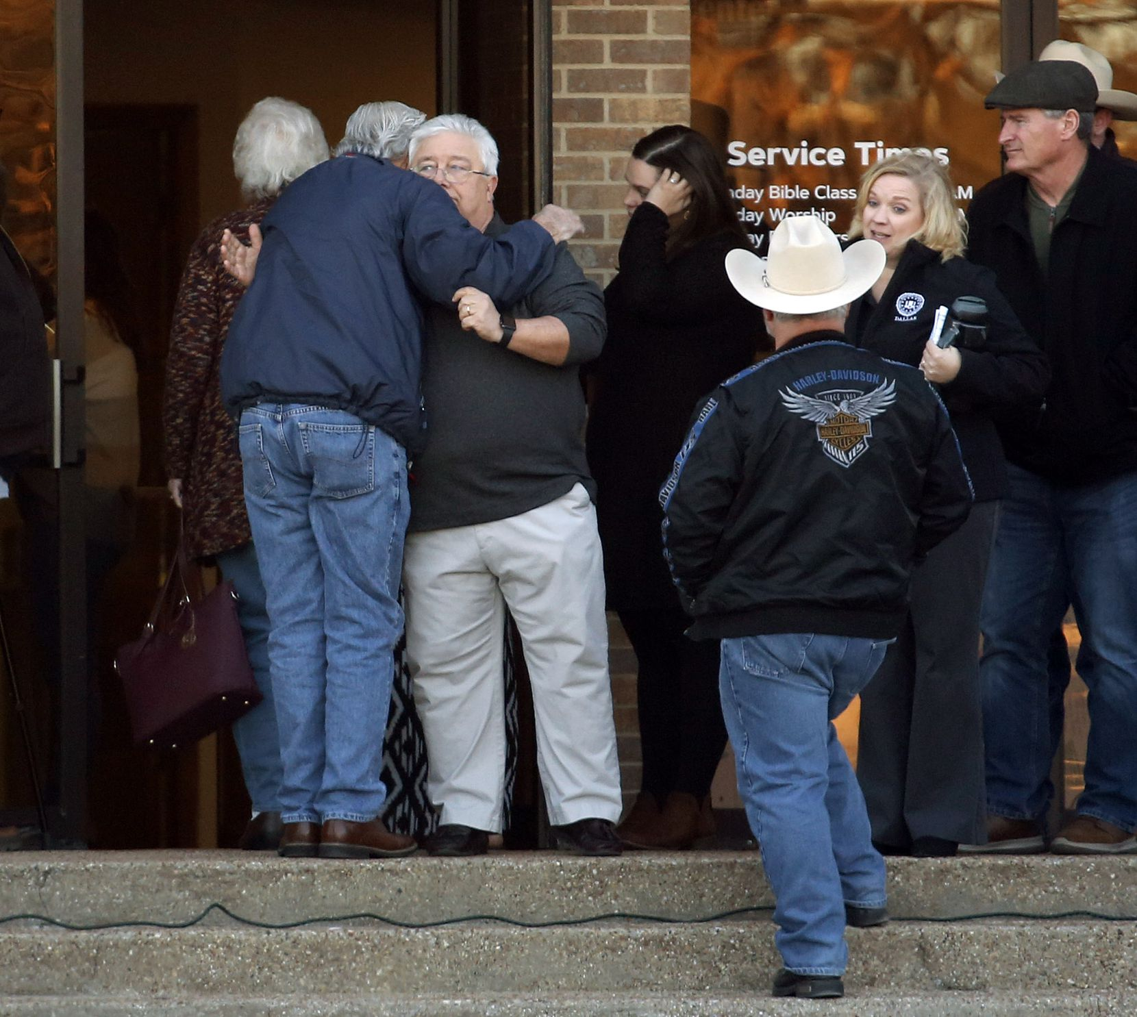Senior minister Britt Farmer (left, facing camera), shown greeting people before a vigil at West Freeway Church of Christ in Fort Worth on Dec. 30, on Monday attended a ceremony in Austin at which Gov. Greg Abbott honored church deacon Jack Wilson. (Tom Fox/The Dallas Morning News)