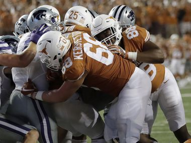 Texas running back Chris Warren III (25) is pushed across the goal line by teammates Derek Kerstetter (68) and Kendall Moore (88) to score a two-yard touchdown in overtime against Kansas State in an NCAA college football game, Saturday, Oct. 7, 2017, in Austin, Texas. Texas won 40-34 in overtime. (AP Photo/Eric Gay)