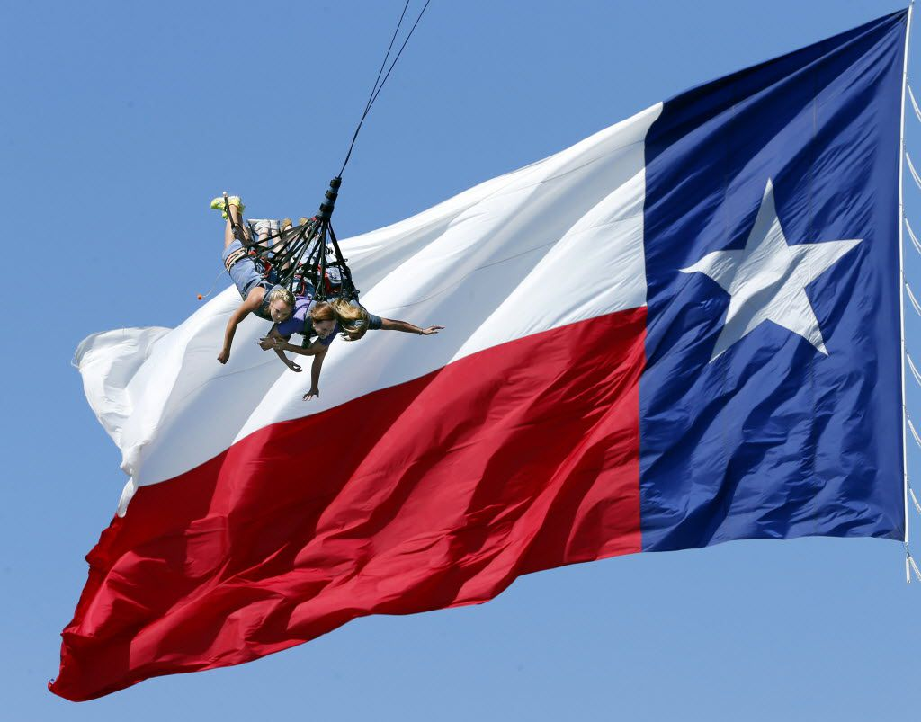"""Sarah Chinners, 16, of Van Alstyne, her sister Megan Chinners and mom Tricia Chinners flyewpast a gigantic Texas flag on the Sky Coaster swing at the State Fair of Texas on Friday. As the trio approached the top of the 189-foot lift, Megan said, """"We're gonna die!"""" Her sister chimed in saying ,""""No we're not!"""" as the cord released."""