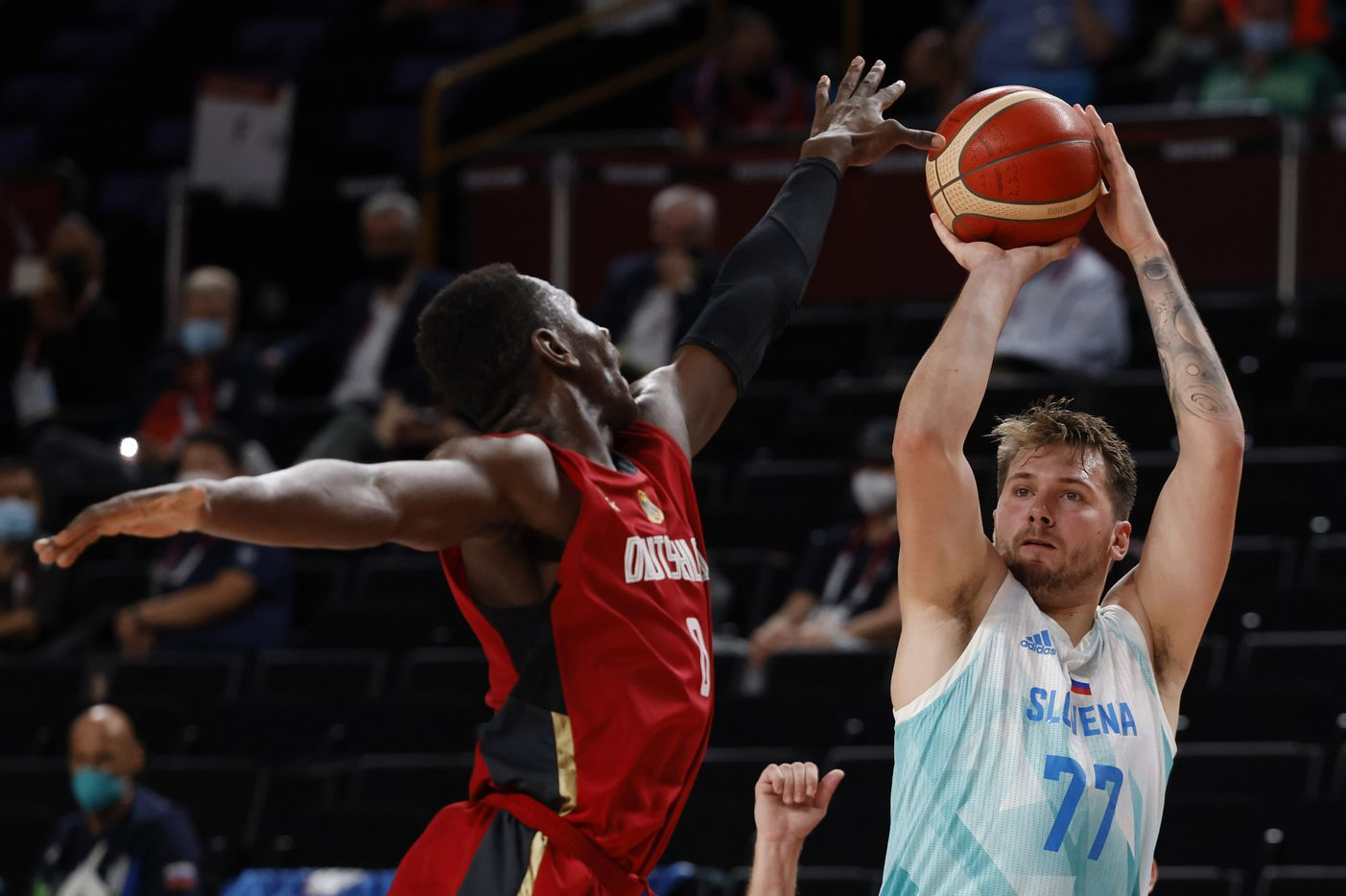 Slovenia's Luka Doncic (77) shoots over Germany's Isaac Bonga (0) during the second half of play of a quarter final basketball game at the postponed 2020 Tokyo Olympics at Saitama Super Arena, on Tuesday, August 3, 2021, in Saitama, Japan. (Vernon Bryant/The Dallas Morning News)