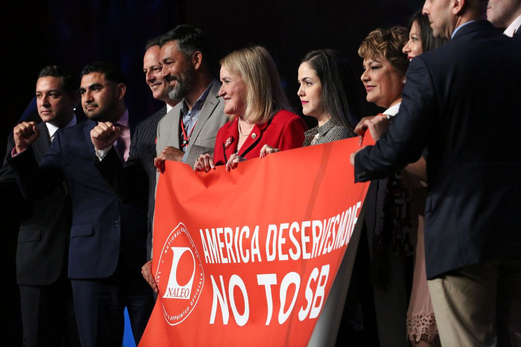 Elected officials pose for a photograph after signing a resolution condemning the enactment of Senate Bill 4 immigration law during the National Leadership Luncheon at the 34th annual NALEO Dallas Conference at the Sheraton Hotel in Dallas on Thursday, June 22, 2017.