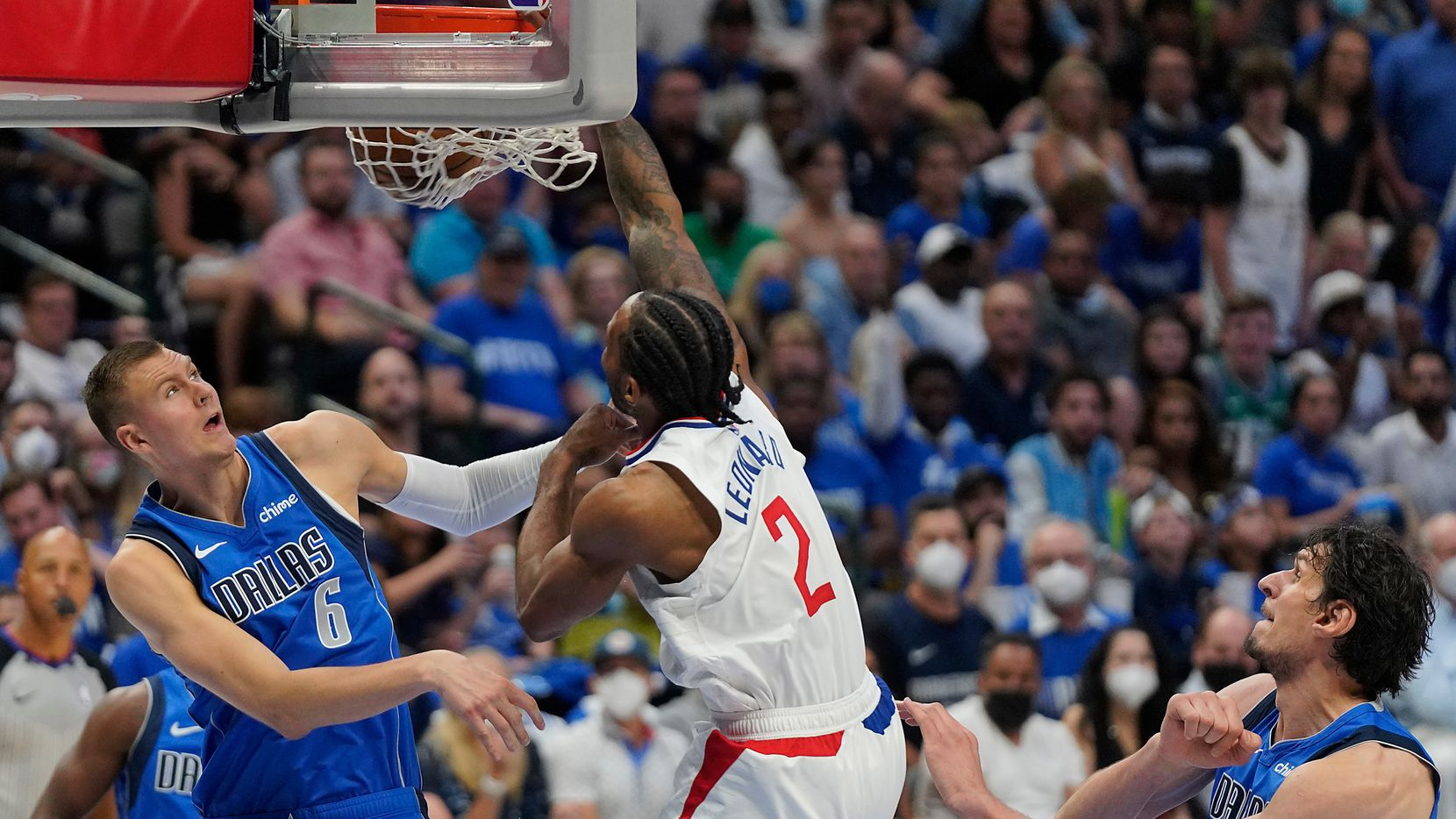 LA Clippers forward Kawhi Leonard (2) dunks the ball past Dallas Mavericks center Kristaps Porzingis (6) during the second half of an NBA playoff basketball game at the American Airlines Center on Friday, June 4, 2021, in Dallas. The Clippers won the game 104-97.