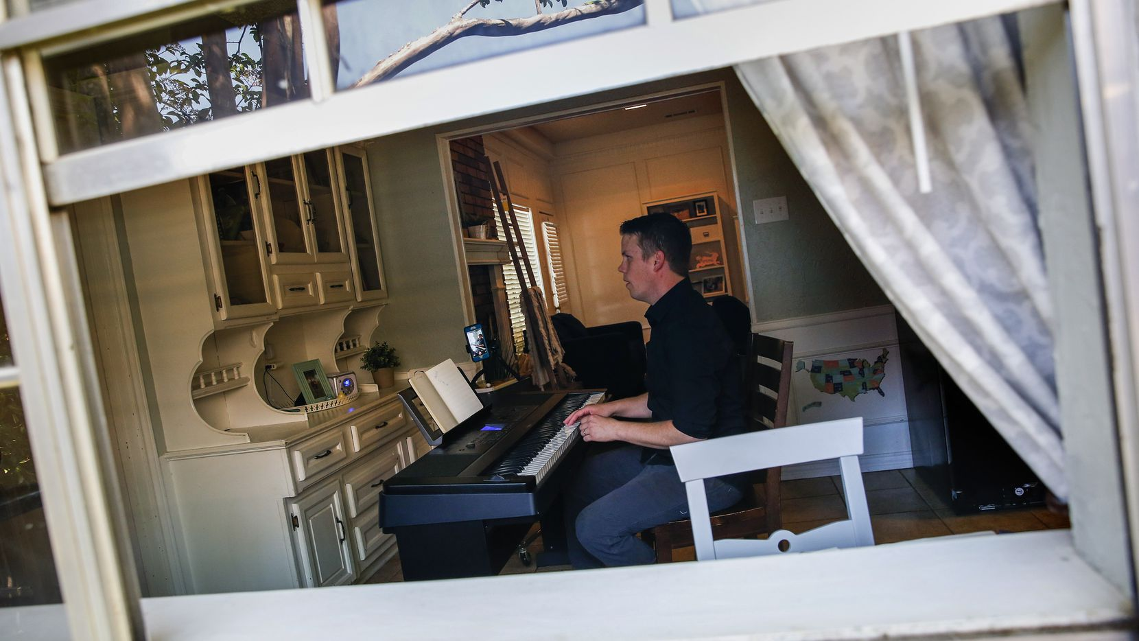 Brad Hanson, who has been playing the piano at NorthPark Mall for 11 years, plays the piano Friday, April 10, 2020 at his home in Garland, Texas. Since the mall is temporarily closed due to the new coronavirus, Hanson has been playing concerts live on Facebook to bring music into people's homes.