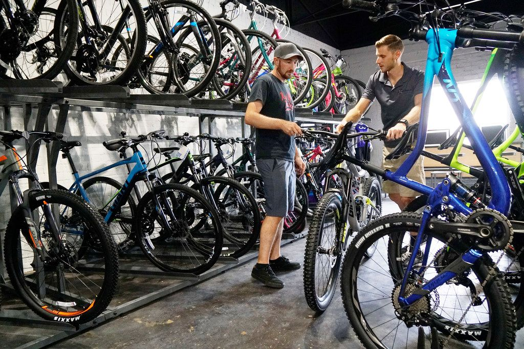 The smell of coffee accompanies the smell of rubber tires. Here, Scott Hofer speaks to Aston Haswell at Cadence Cyclery, which doubles as Vero Cafe in Keller.