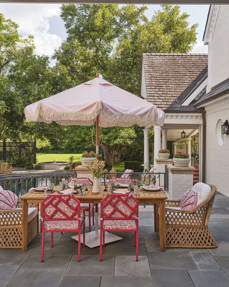 The outdoor terrace off the back of the 2021 Kips Bay Decorator Show House Dallas features pops of pink and pattern. The space was designed by Robin Henry Studio and it surrounds the pool, providing multiple opportunities for living, dining and lounging outside.
