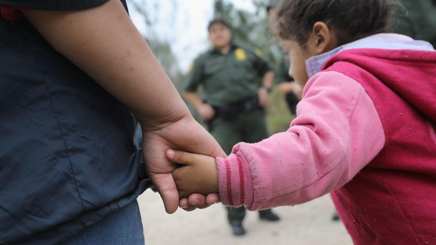 Un agente de la Patrulla Fronteriza detiene a una familia con niños que intentó ingresar a Estados Unidos por el sector de McAllen, al sur de Texas.(GETTY IMAGES)