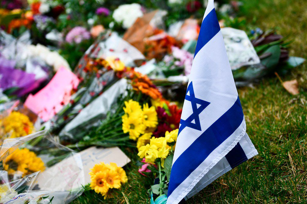 """An Israeli national flag is seen at a memorial on October 28, 2018, down the road from the Tree of Life synagogue after a shooting there left 11 people dead in the Squirrel Hill neighborhood of Pittsburgh on October 27, 2018. - A man suspected of bursting into a Pittsburgh synagogue during a baby-naming ceremony and gunning down 11 people has been charged with murder, in the deadliest anti-Semitic attack in recent US history. The suspect -- identified as a 46-year-old Robert Bowers -- reportedly yelled """"All Jews must die"""" as he sprayed bullets into the Tree of Life synagogue during Sabbath services on Saturday before exchanging fire with police, in an attack that also wounded six people."""