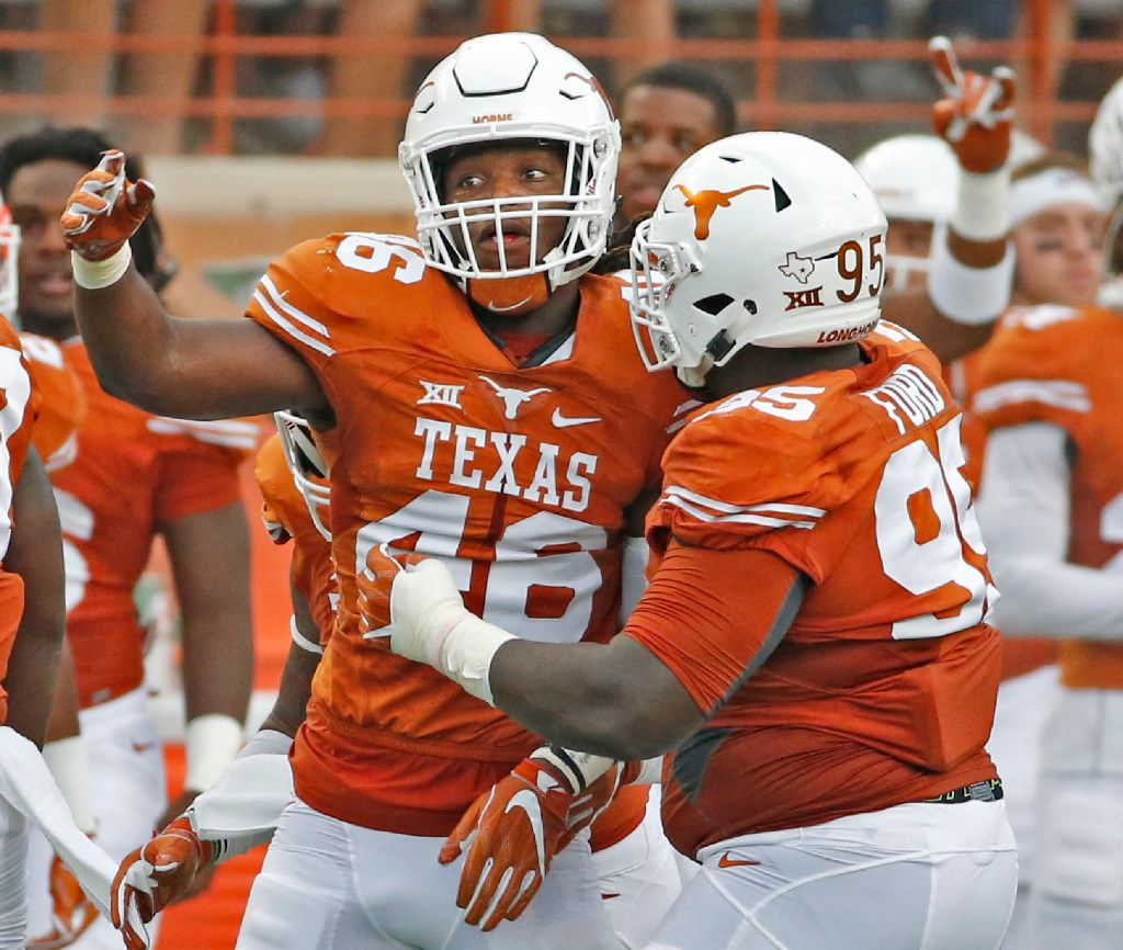 Texas linebacker Malik Jefferson (46) and defensive tackle Poona Ford (95) celebrate a defensive stop during the Notre Dame Fighting Irish vs. the University of Texas Longhorns NCAA football game at Darrell K. Royal Memorial Stadium in Austin on Sunday, September 4, 2016. (Louis DeLuca/The Dallas Morning News)
