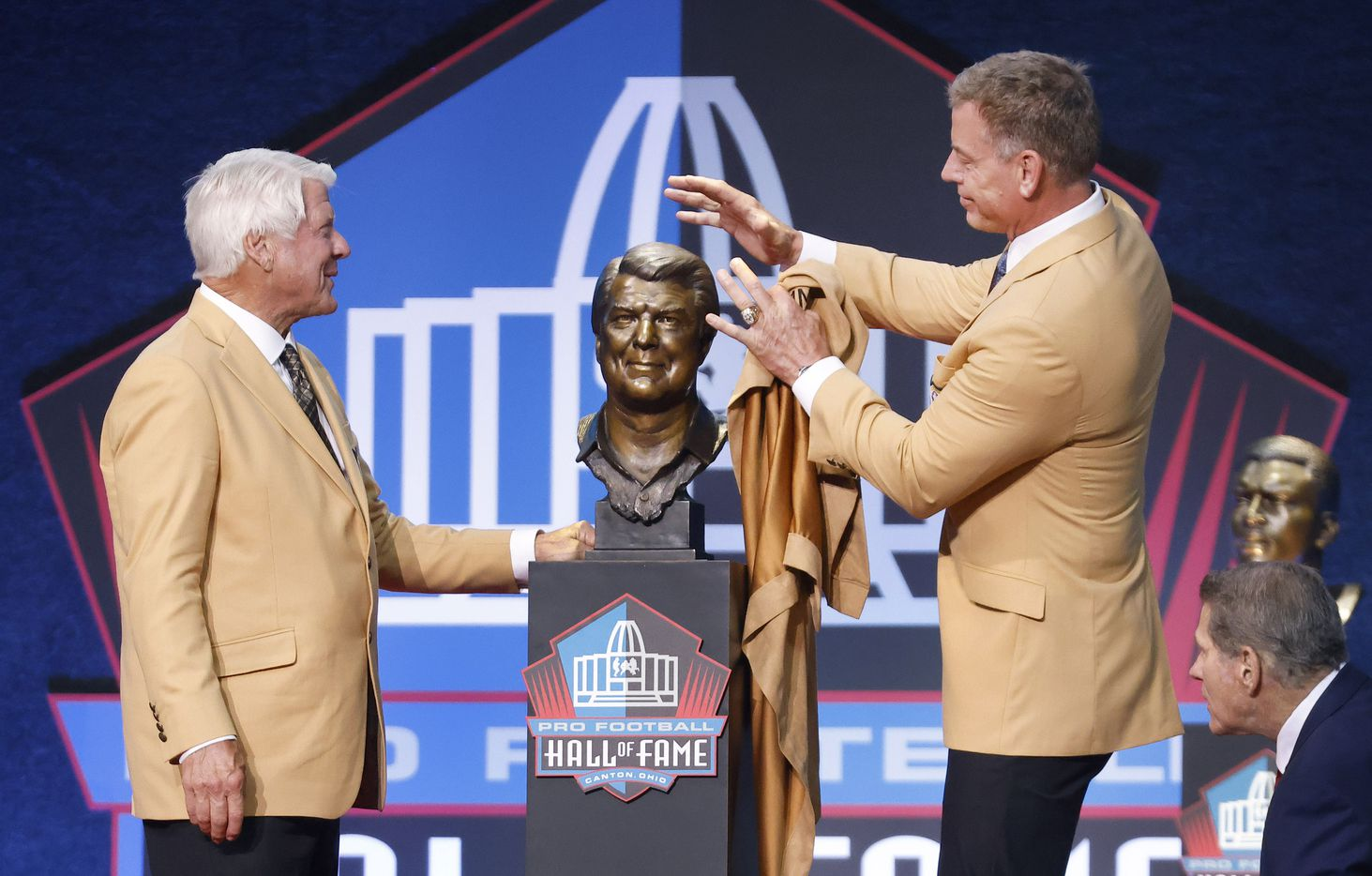 Presenter and former Dallas Cowboys Pro Football Hall of Fame quarterback Troy Aikman teasingly attempts to mess up inductee Jimmy Johnson's bronze hair following the bust reveal during the Centennial Class of 2020 enshrinement ceremony at Tom Benson Hall of Fame Stadium in Canton, Ohio, Saturday, August 7, 2021. (Tom Fox/The Dallas Morning News)