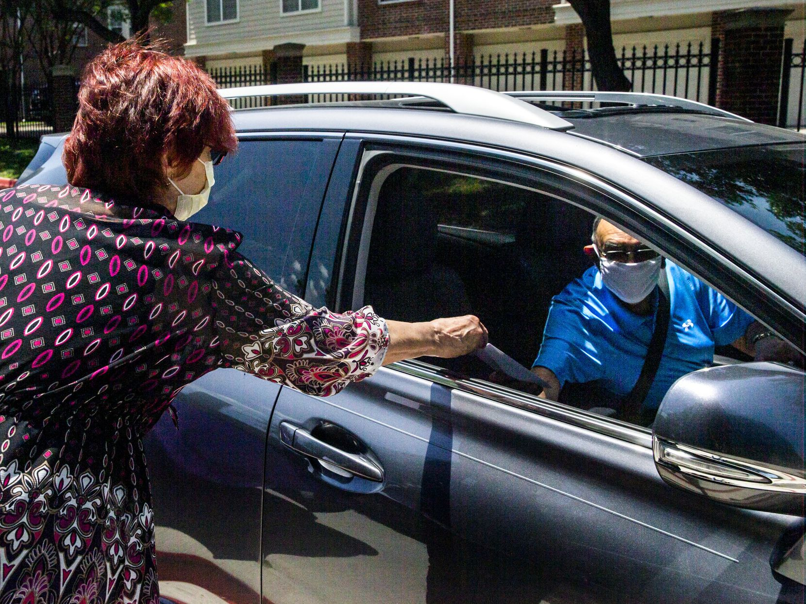 Director of social services Linda Daugherty (left) makes a hand-off to Richard King as supporters picked up the gold ribbons in the May drive-through event.
