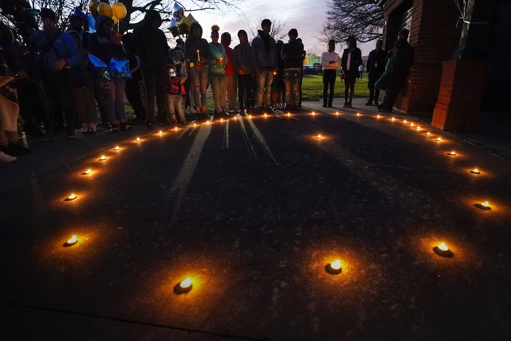 """Mourners gather for a vigil for Marc """"Flea"""" Strickland, the 18-year-old victim of a shooting at Dallas ISD basketball game, as the sun sets at Bushman Park on Sunday, Jan. 19, 2020, in Dallas."""