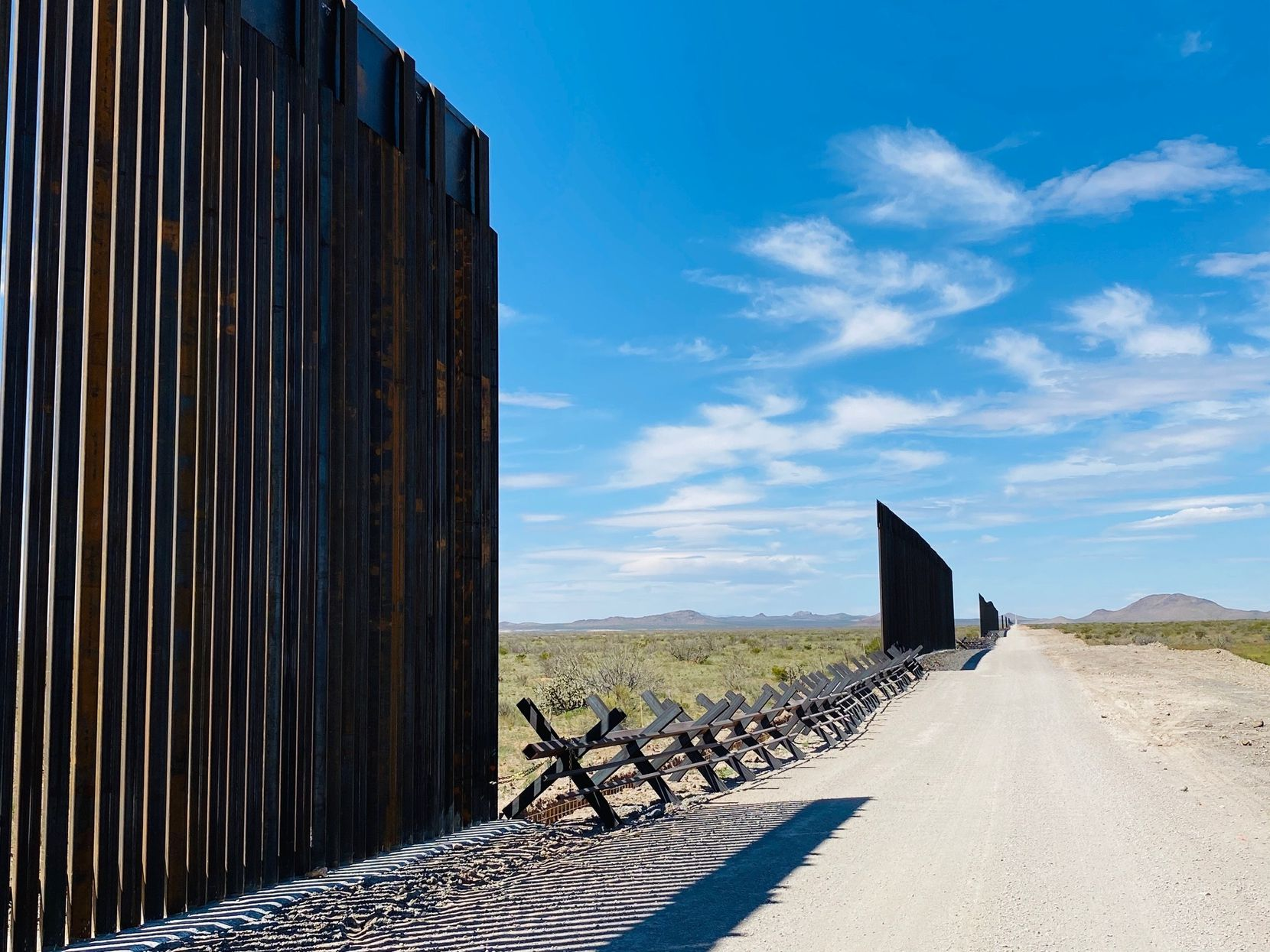 With the pace of border wall construction lagging behind President Donald Trump's goal of completing 500 miles by year's end, new fencing is slowly replacing old barriers, with gaps in between, near Highway 9 near Columbus, N.M.