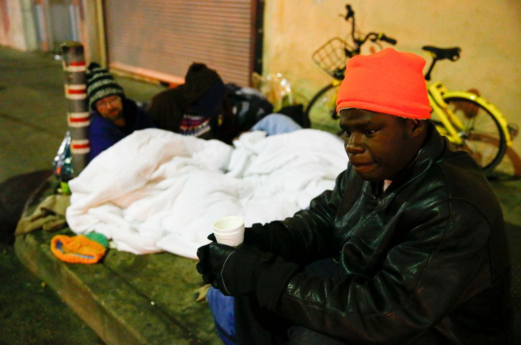 Dawaylon Raymond, 20, (right) drinks some donated coffee as Ryan Rule, 39, (left) and his wife, Deshonda Rule, 33, sleep on top of an exhaust vent next to The Stewpot on Park Ave in downtown Dallas on Jan. 16, 2018, when temperatures fell into the teens throughout the night.