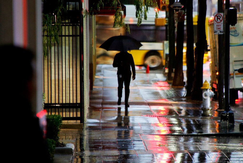 A man makes his way down Commerce street through wet and cold conditions as temperatures dropped into the 40's in downtown Dallas on Monday, October 15, 2018.