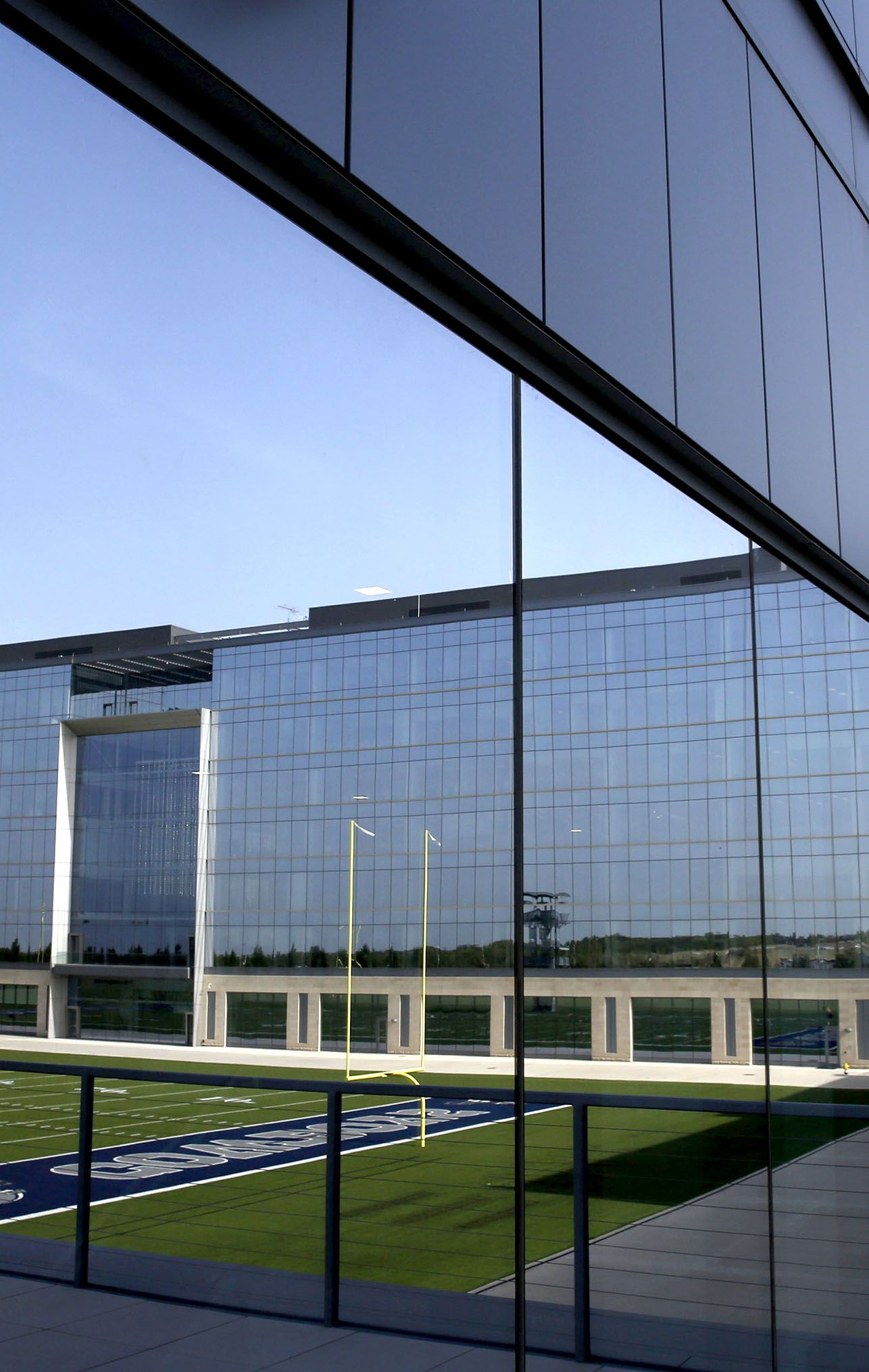 An outdoor practice field is reflected in the glass of the Dallas Cowboys headquarters building, at The Star in Frisco, Texas on July 17, 2018.