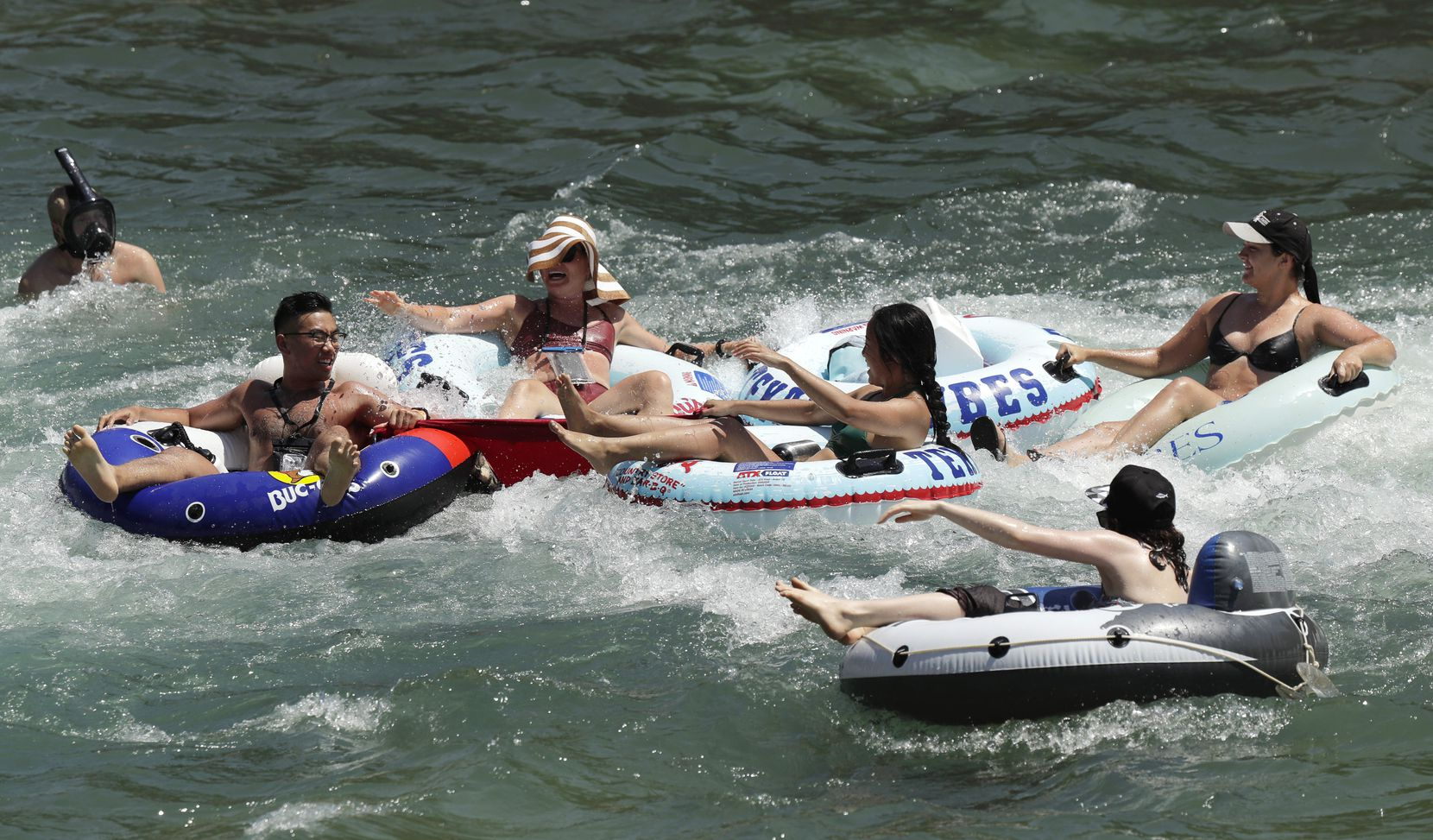 Tubers float the Comal River in New Braunfels Wednesday. As parks reopen following closures due to the COVID-19 pandemic, many Texans are returning to the outdoors.