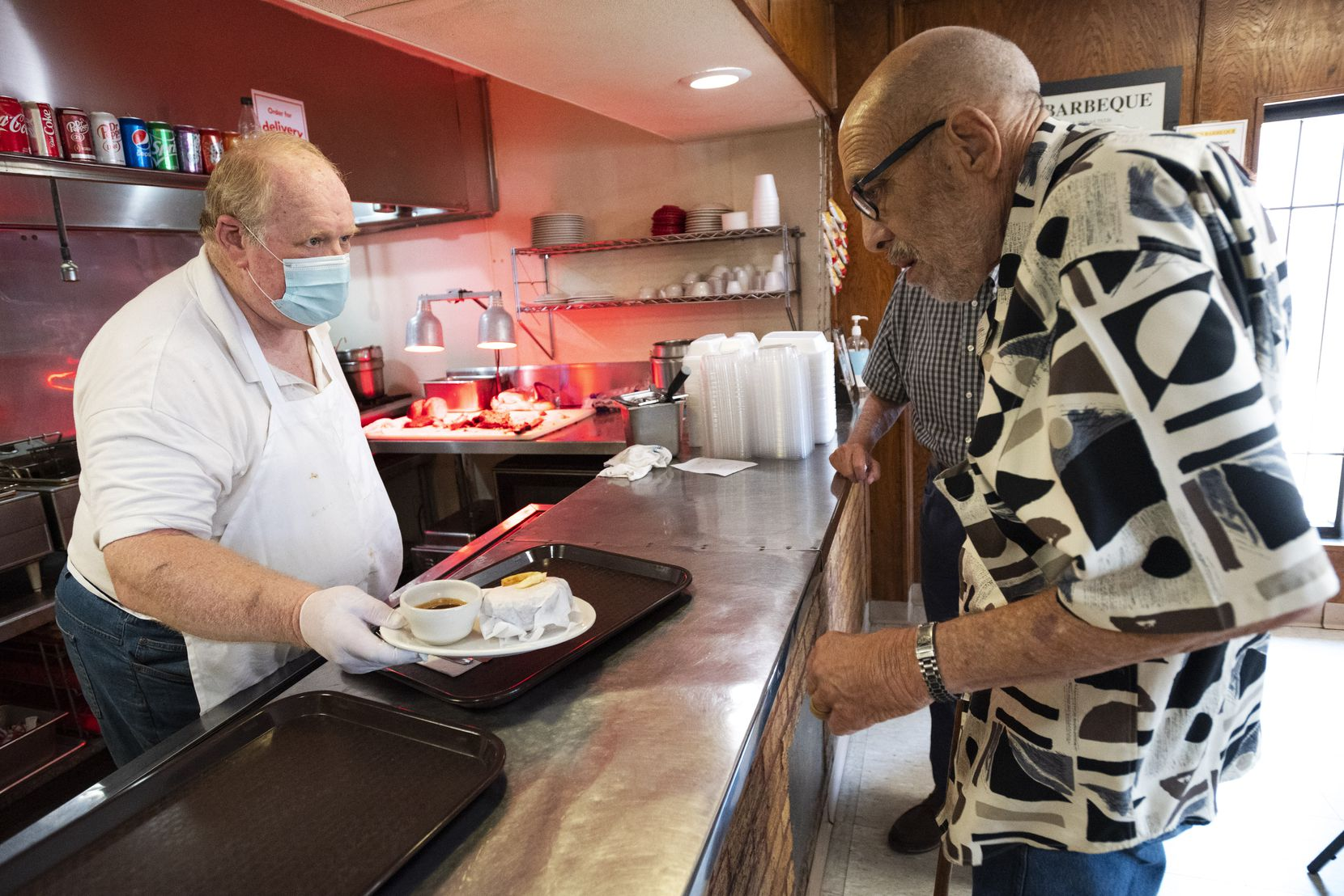 Owner Billy McDonald, left, serves a food order to longtime customer Herschel Wilonsky on one of the last days of business at Mac's Bar-B-Que in Dallas.