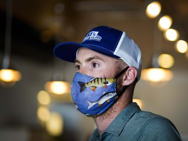Bar manager Brett Martin wears a fish-themed face mask at TJ's Seafood restaurant on Tuesday, May 19, 2020, in Dallas. With the need for face masks high, the Far-More Shade pet bed company has added masks to their repertoire – with many featuring colorful patterns. (Smiley N. Pool/The Dallas Morning News)