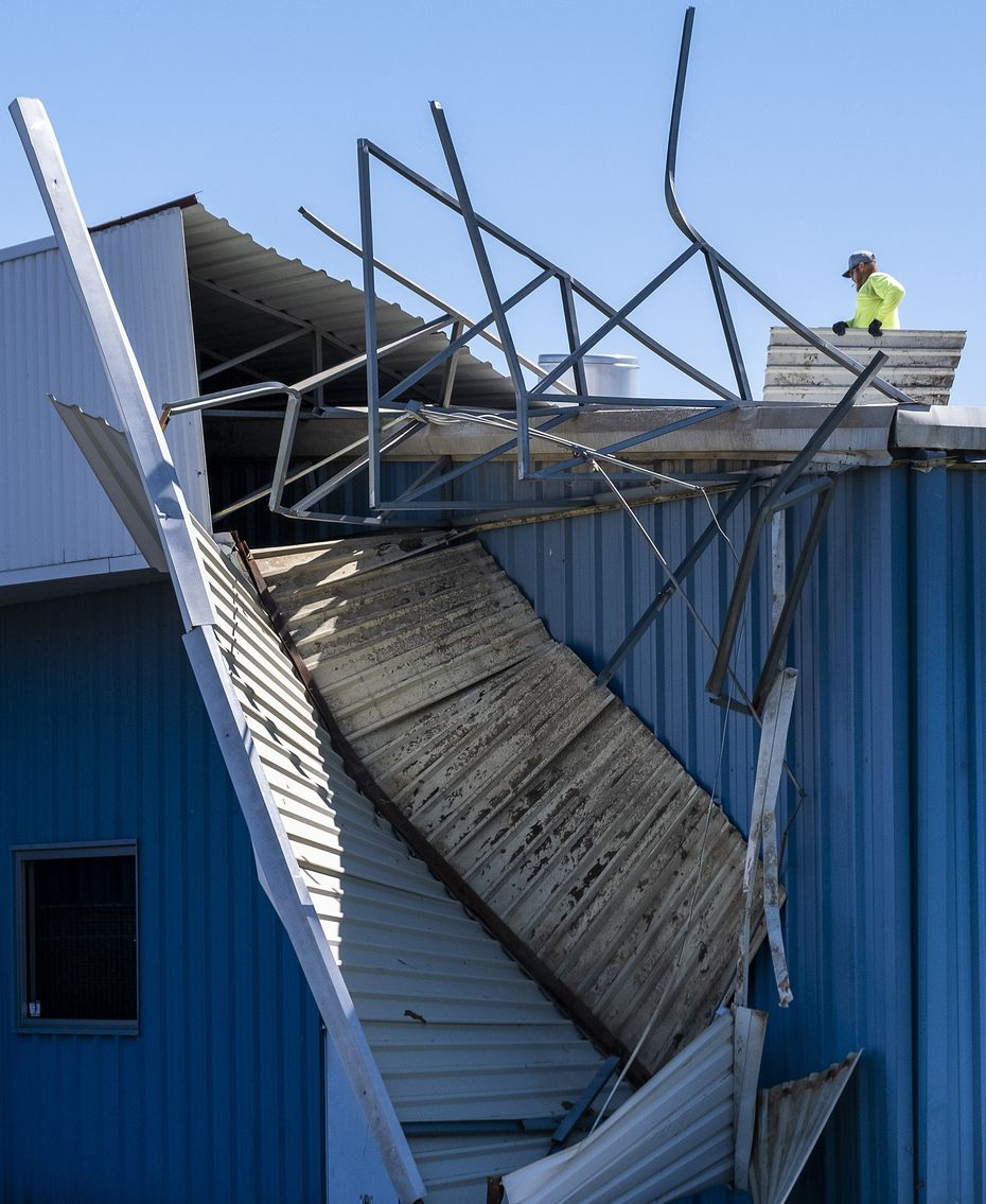 Workers clear sheet metal from the roof of Polymer Products in Grand Prairie, which suffered storm damage.