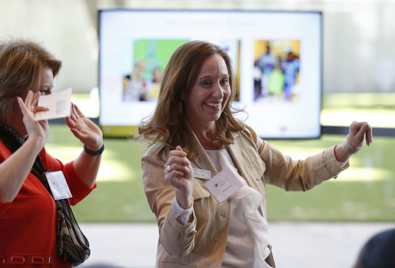 Allen Community Outreach's Amy Gnadt (left) and Rhonda Ptak dance their way back to their seats after picking up a check they received during the The Dallas Morning News Charities 2019-20 Campaign Kickoff Reception at Winspear Opera House in Dallas.