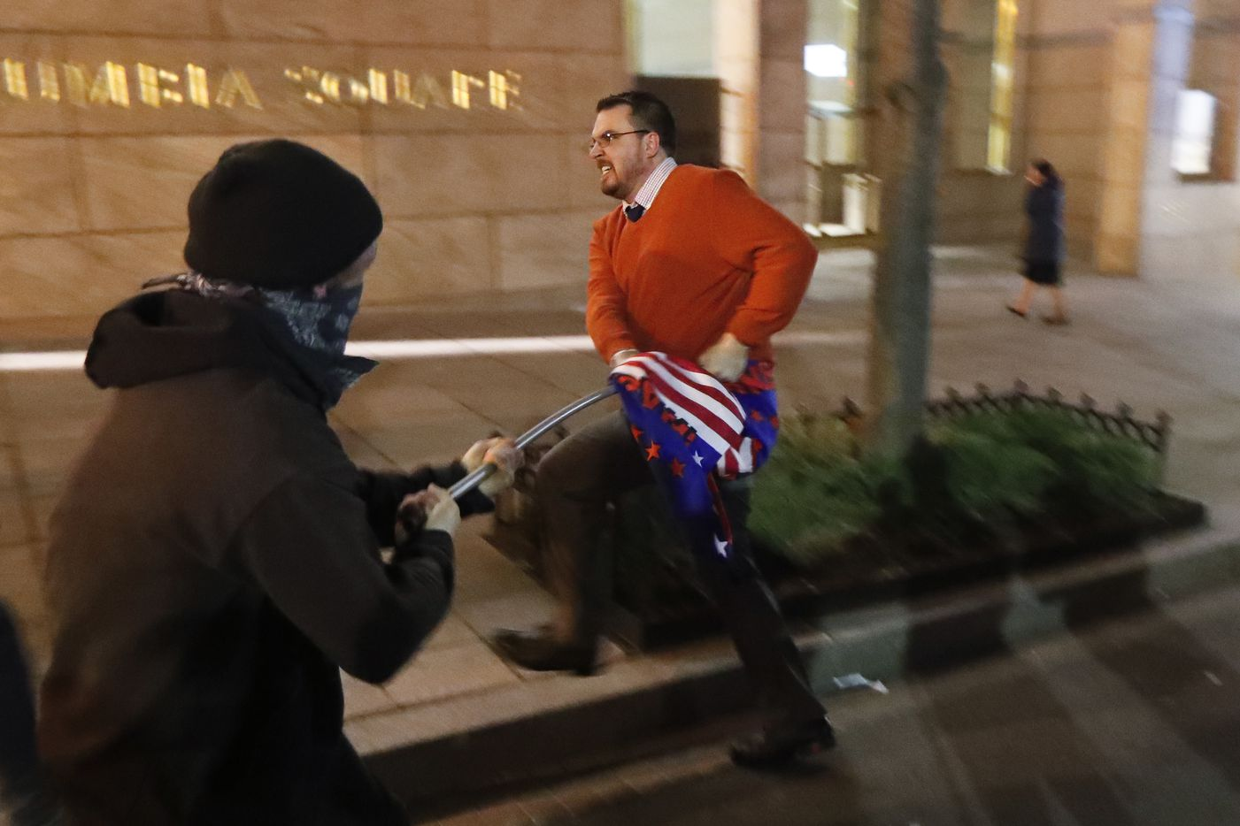A protester tries to take aTrump supporter's campaign flag during a demonstration ahead of the presidential inauguration, Thursday, Jan. 19, 2017, in Washington.