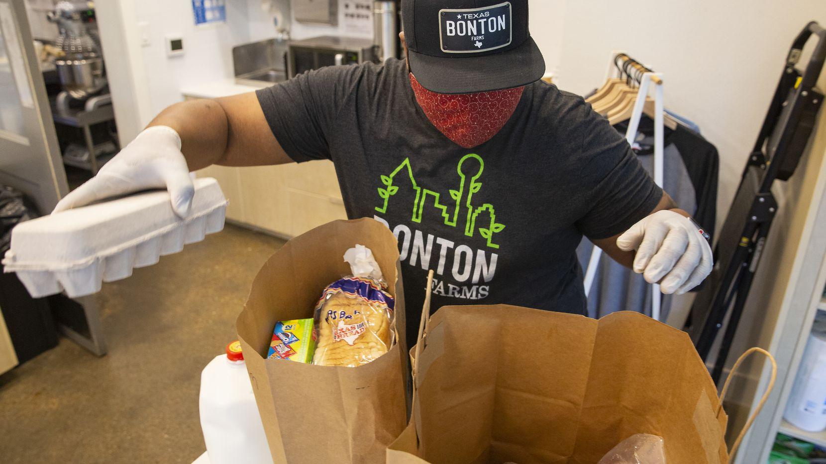 Clifton Reese, administrador en The Market at Boston Farms, prepara bolsas con alimentos para ser entregados a padres de familia con estudiantes en The King's Academy.