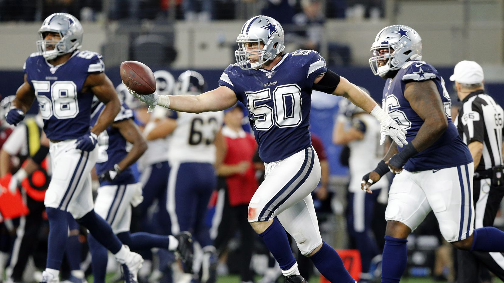 FILE — Dallas Cowboys outside linebacker Sean Lee (50) extends his arm to hand quarterback Dak Prescott (not pictured) the ball after making an interception at AT&T Stadium in Arlington, Texas, Sunday, December 15, 2019.
