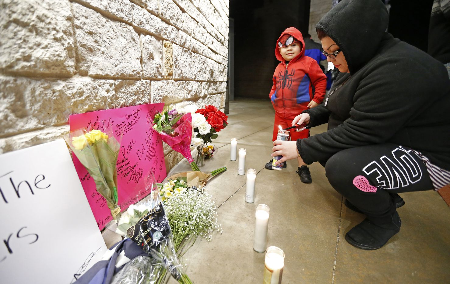 Roxie Murillo lights a candle with her 4-year-old son, Julian Ruiz, at a memorial for Detective Jerry Walker outside the Little Elm police headquarters. (Jae S. Lee/Staff Photographer)