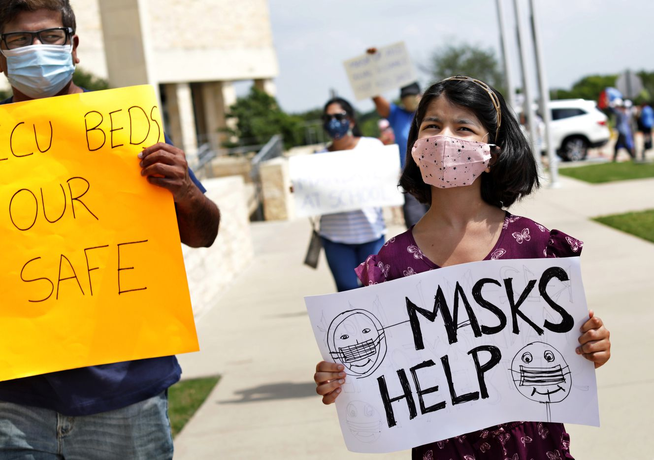 Devang Shah, left, and 8-year-old Khushi Shah join other community members seeking better COVID-19 protections during a protest at the Frisco ISD Administration Building in Frisco, TX, on Aug. 26, 2021.