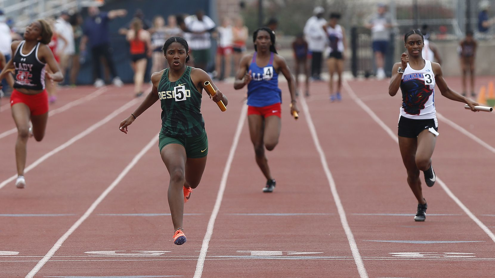 Mia Abraham (center) crosses the finish line first for DeSoto in the girls 4x100-meter relay at the Jesuit-Sheaner Relays on Saturday.