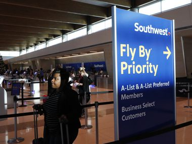 Southwest Airlines passengers checks-in using a kiosk, background, at Dallas Love Field in Dallas, Thursday, December 1, 2016. (David Woo/The Dallas Morning News)