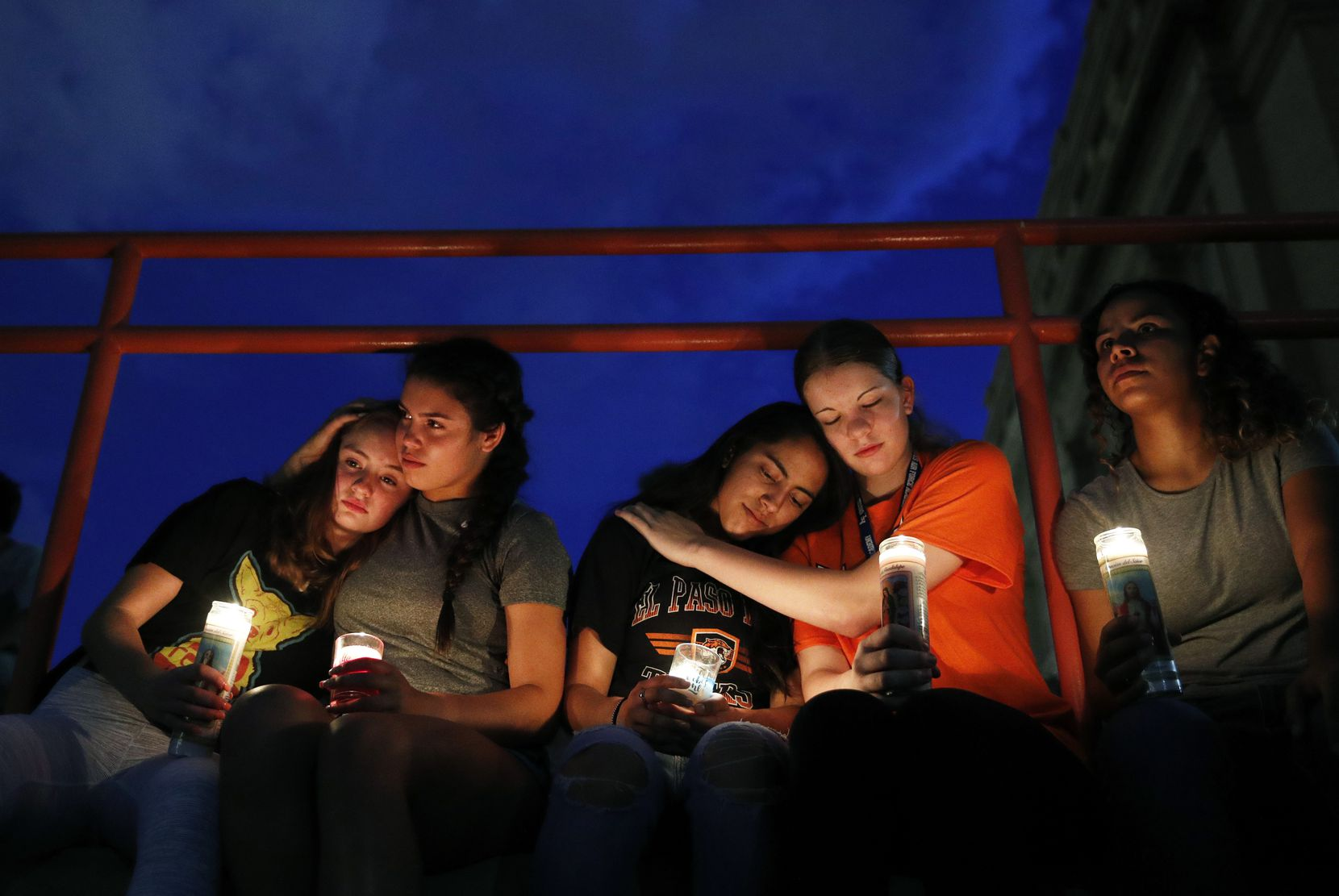 From left: Melody Stout, Hannah Payan, Aaliyah Alba, Sherie Gramlich and Laura Barrios comfort each other during a vigil for victims of the shooting Saturday, Aug. 3, 2019, in El Paso. A young gunman opened fire in an El Paso shopping area during the busy back-to-school season, leaving multiple people dead and more than two dozen injured.