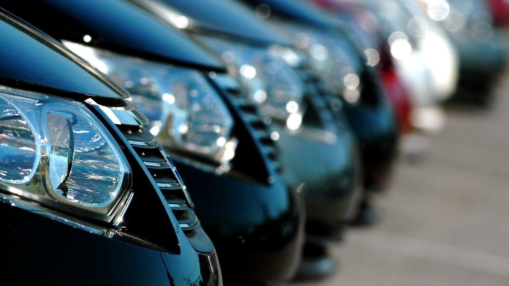 Fila de vehículos  en una agencia de autos nuevos.