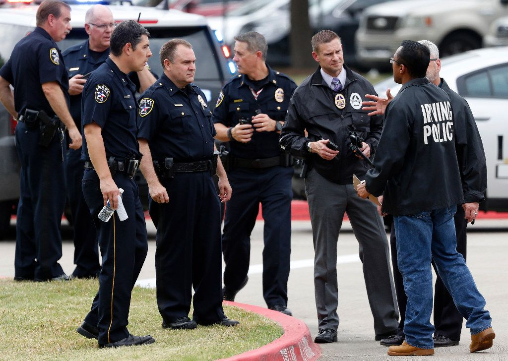 Irving police officers work at the shooting scene.