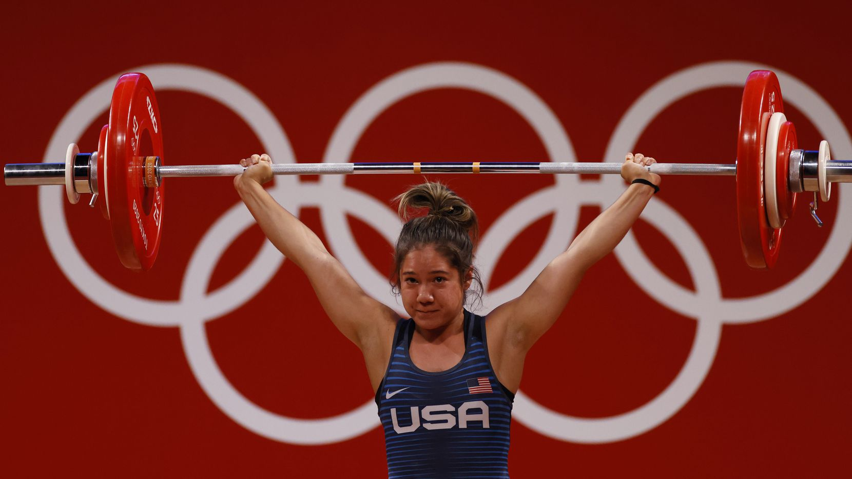 USA's Jourdan Delacruz competes in the first attempt of the snatch round during the women's 49 kg weightlifting final  during the postponed 2020 Tokyo Olympics at Tokyo International Forum on Saturday, July 24, 2021, in Tokyo, Japan. (Vernon Bryant/The Dallas Morning News)