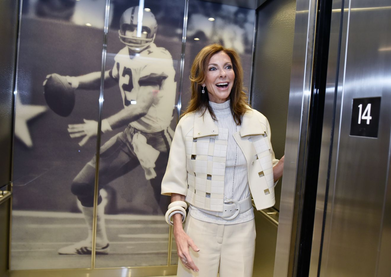Charlotte Jones walks into an elevator decorated with a giant image of former Dallas Cowboys quarterback Roger Staubach, as she conducted a tour of the Twelve Cowboys Way luxury residential tower at the Star in Frisco.