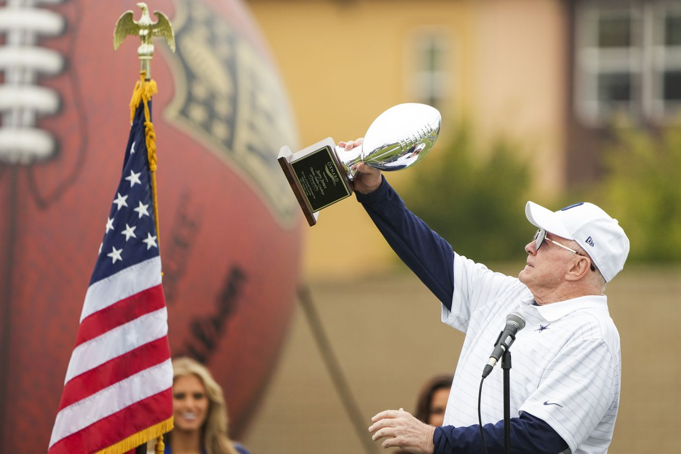 Dallas Cowboys owner and general manager Jerry Jones lifts a trophy presented to him by Oxnard Mayor John Zaragoza during opening ceremonies before a practice at training camp on Saturday, July 24, 2021, in Oxnard, Calif.