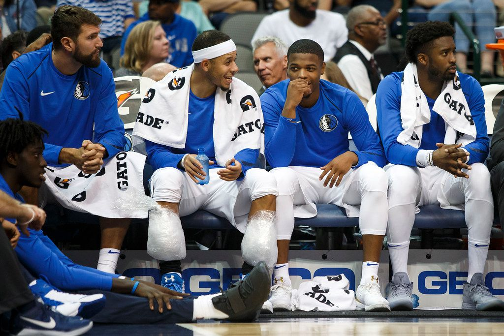 Dallas Mavericks guard Dennis Smith Jr. (second from right) laughs with guard Seth Curry (with ice on knees) as they watch from the bench during the first half of an NBA preseason basketball game against the Milwaukee Bucks at American Airlines Center on Monday, Oct. 2, 2017, in Dallas. (Smiley N. Pool/The Dallas Morning News)