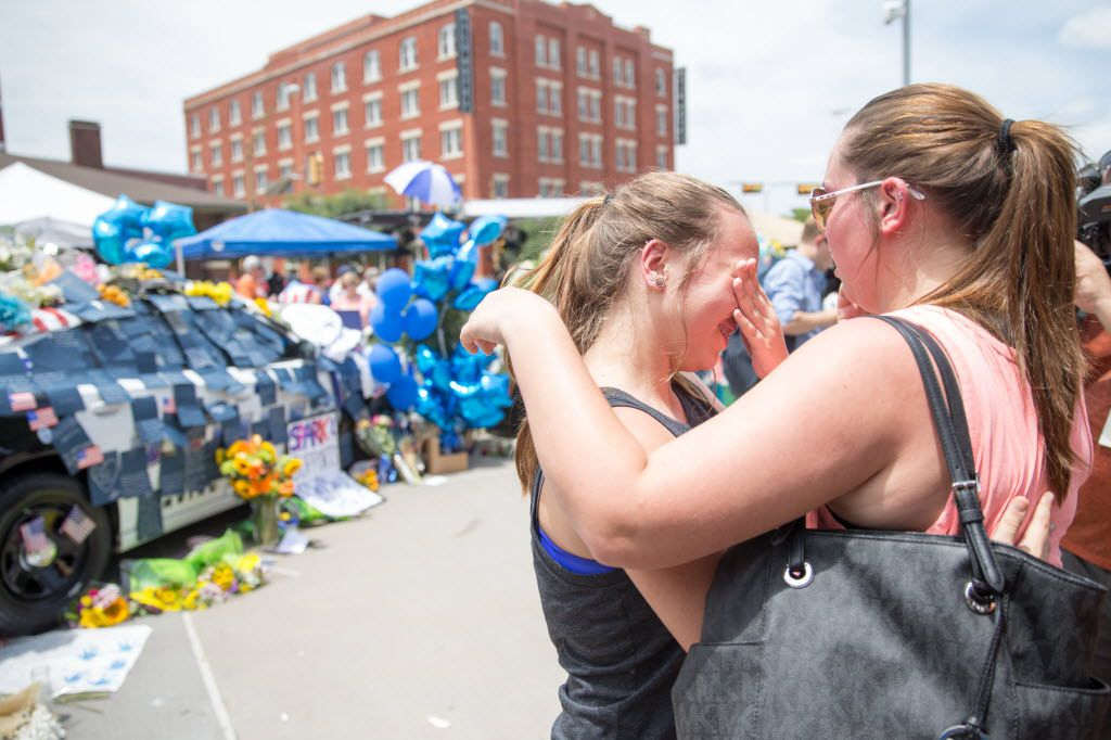 Abbey Wheeler, 14, wipes away tears as her  sister Madison Wheeler, 19, comforts her in front of the memorial for the slain officers at theDallas Police Headquarters on July 9, 2016 in Dallas. (Ting Shen/The Dallas Morning News)