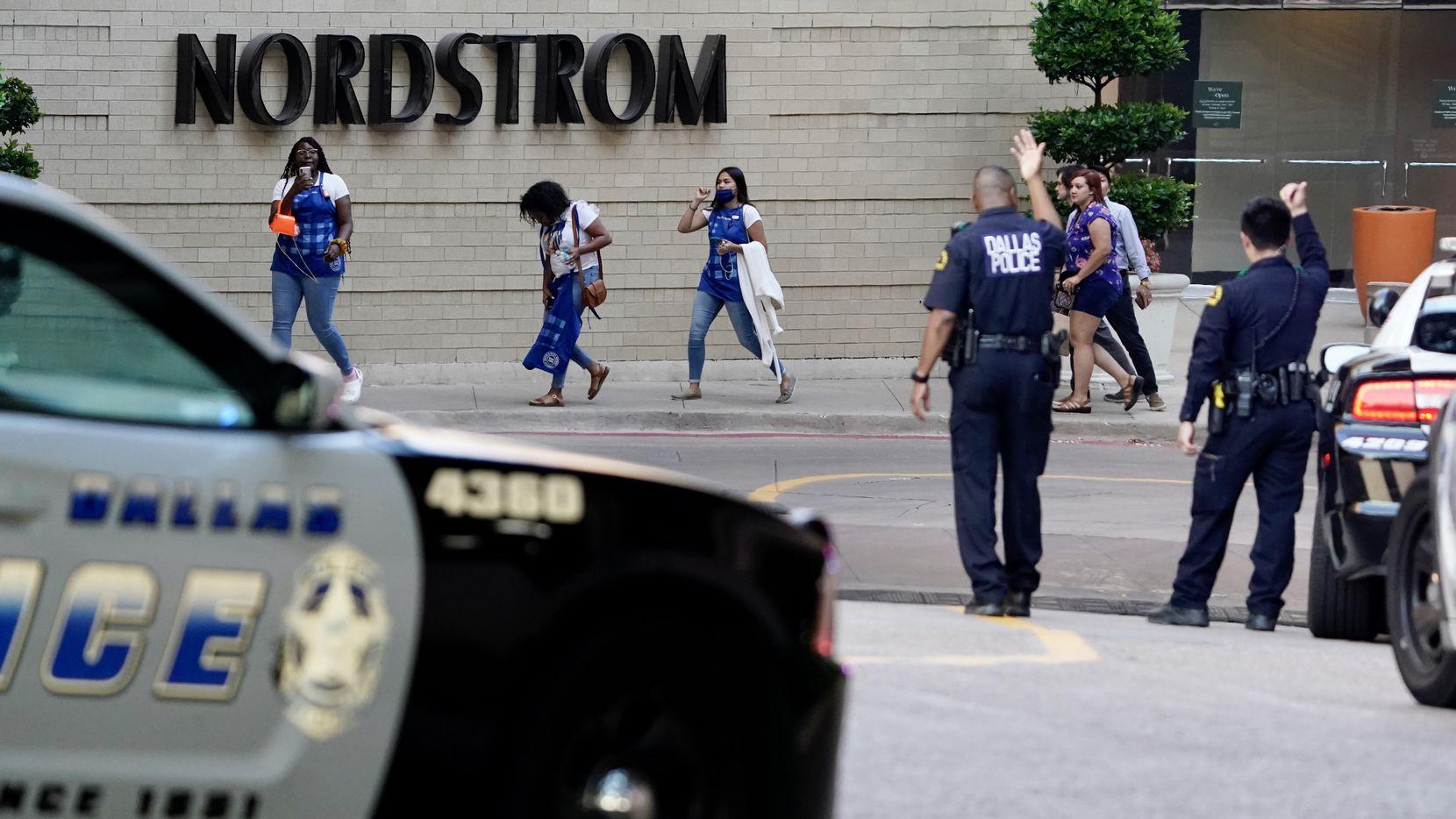 La policía de Dallas da direcciones a personas que evacúan el Gallería Mall al norte de Dallas. El martes hubo un tiroteo que dejó al menos un herido.––