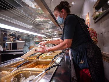 Server Gopanandini prepares a to go order for a customer inside Kalachandji's vegetarian restaurant on Gurley Avenue in east Dallas, on Saturday, Aug. 28, 2021. Kalachandji's is one of Dallas' last buffets.