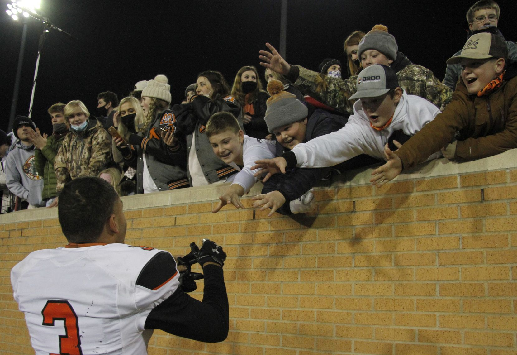 Aledo running back Jeremiah James (3) draws the attention of young Bearcats fans as they scramble for the chance to snag a game souvenir when he decides to part with his gloves following Aledo's 55-28 victory over Wichita Falls Rider to advance to the state tournament. The two teams played their Class 5A Division ll state semifinal football playoff game at Apogee Stadium in Denton on January 8, 2021. (Steve Hamm/ Special Contributor)