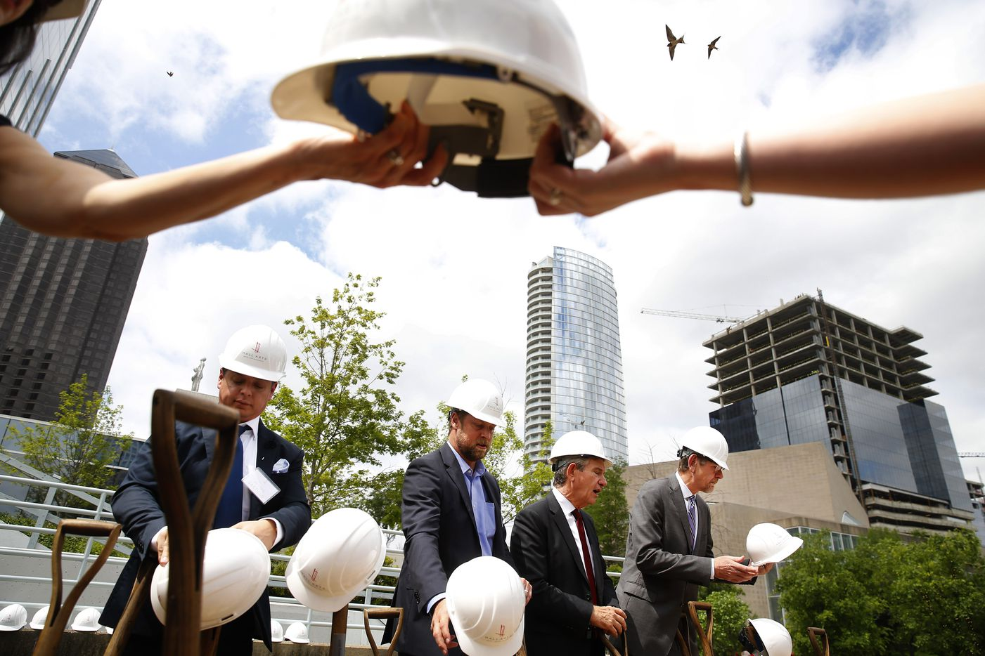 Helmets are passed during a photo opportunity during the ground breaking ceremony on Hall Arts Hotel and Residences.