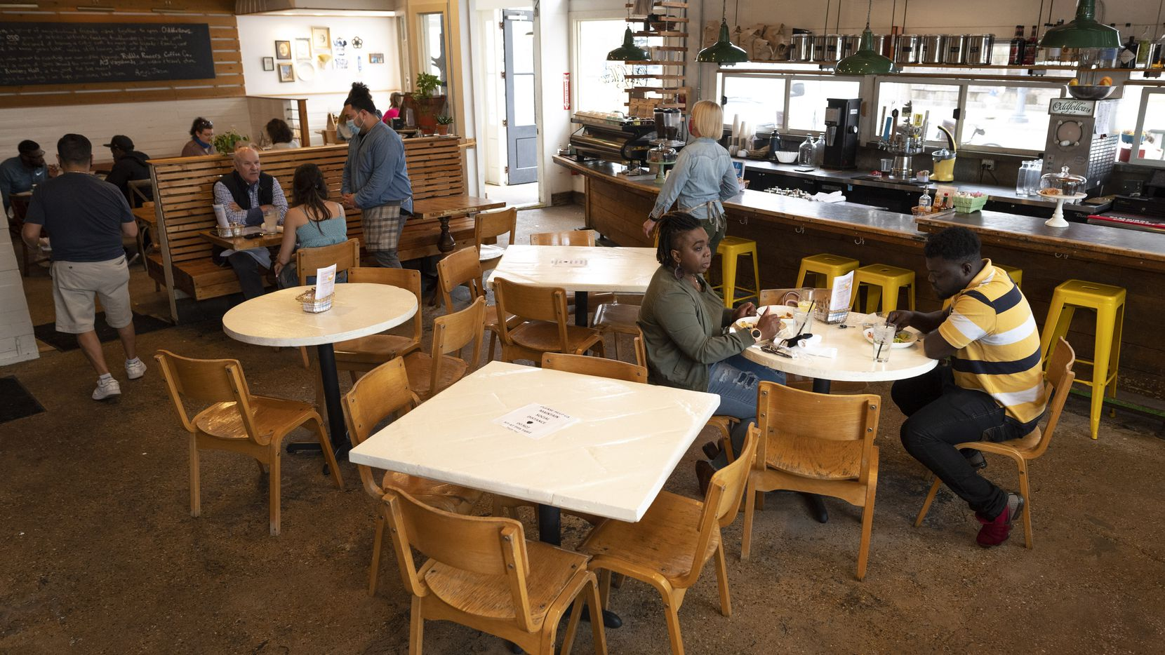 Shanita Brown (right) and James Quayson, 31 (far-right(, have lunch inside Oddfellows restaurant at the Bishop Arts District in Dallas on the first day the mask mandate and occupancy limits are lifted. Oddfellows is still operating at 75% capacity and all employees must wear face masks.