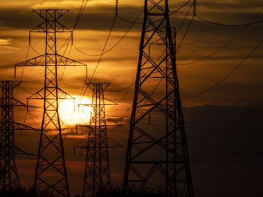 The sun sets behind electricity towers along Mountain Creek Parkway in Dallas on Wednesday, June 30, 2021.