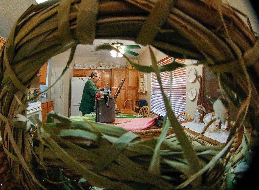 A wreath made of cattail reeds frames Mike Turrentine as he reweaves a child's rocking chair in the kitchen of his Garland home.