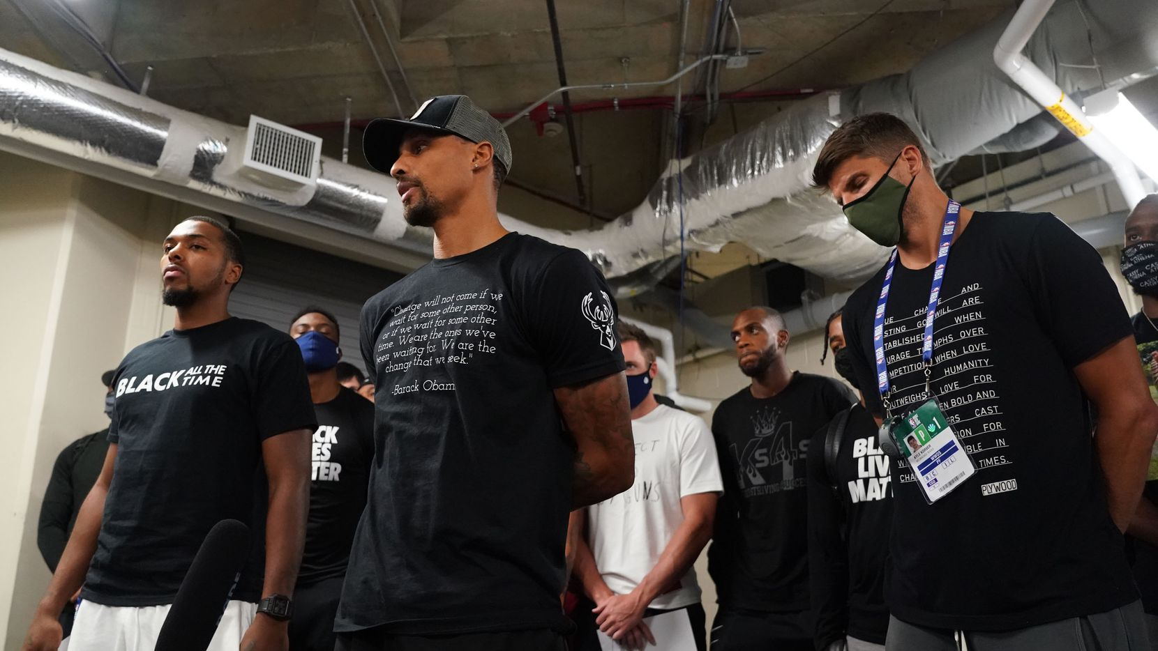 Sterling Brown (far left), with George Hill (second from left), of the Milwaukee Bucks reads a statement to the media on Aug. 26, 2020 at AdventHealth Arena at ESPN Wide World of Sports Complex in Orlando, Fla.