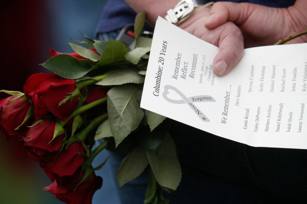 A woman holds a bouquet of roses and a program bearing the names of the victims of the massacre at Columbine High School 20 years ago during an event to mark the incident April 20, 2019, in Littleton, Colo.